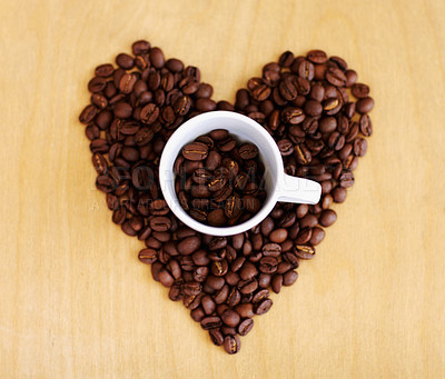 Buy stock photo High angle shot of a cup mug full of coffee beans surrounded by other beans laid out in the shape of a hear
