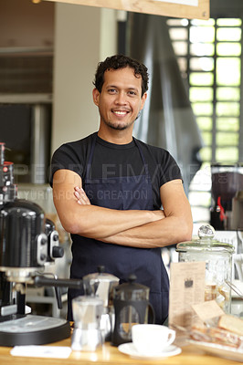 Buy stock photo Shot of a handsome barista standing behind his coffee bar with his arms crossed