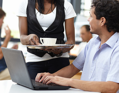Buy stock photo Shot of a waitress delivering a coffee to a man working on a laptop