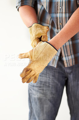 Buy stock photo Cropped image of a handyman putting on gloves