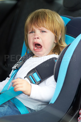 Buy stock photo Portrait of a young baby crying while strapped into a car seat