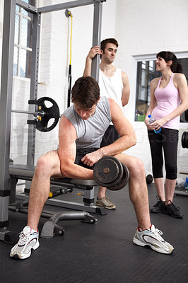 Buy stock photo young bodybuilder lifting a weight while two people chat behind him in the gym