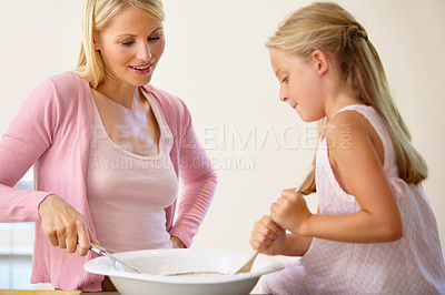 Buy stock photo A mother and daughter stirring a bowel of batter together while baking