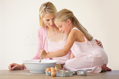 Buy stock photo A little girl kneeling on a kitchen counter and stirring batter while her mother looks on with loving support