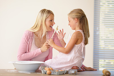 Buy stock photo A mother and daughter having fun and joking around while baking together