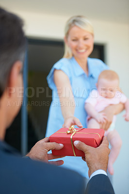 Buy stock photo Cropped shot of a man surprising his wife with a gift