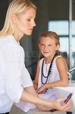 Buy stock photo Little girl watching her mother apply her make-up