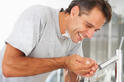Buy stock photo A mature man washing his face in the basin