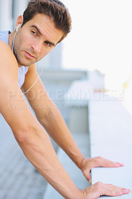 Buy stock photo Cropped image of a handsome young man leaning on a wall