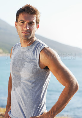 Buy stock photo Sweaty young jogger looking at the camera with his hand on his hip