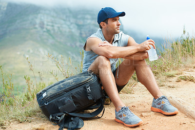 Buy stock photo Young hiker sitting down and taking a moment to rest