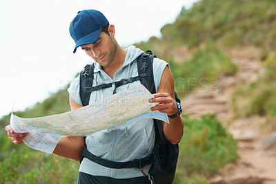 Buy stock photo Young male hiker reading a map