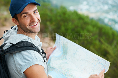 Buy stock photo Happy young hiker smiling at the camera while holding a map