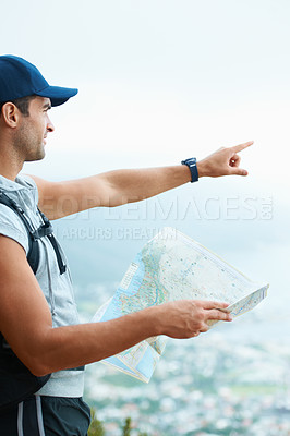 Buy stock photo Young hiker determining his position on a map with the coastline in the background