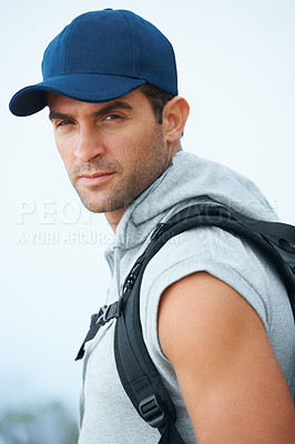 Buy stock photo Handsome young hiker wearing a baseball cap looking straight at the camera