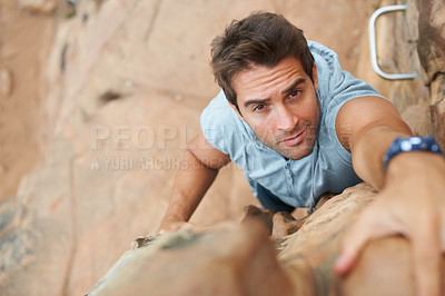 Buy stock photo Handsome young mountain climber scaling a cliff - high angle view