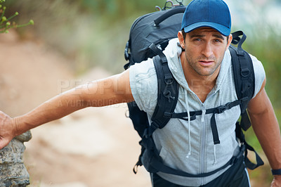 Buy stock photo Handsome young hiker looking up at the camera