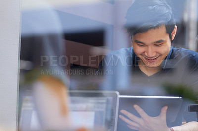 Buy stock photo Smiling Asian man using a digital tablet indoors