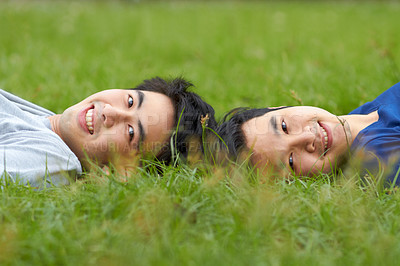 Buy stock photo Cute young gay Asian couple smiling together while lying on the grass