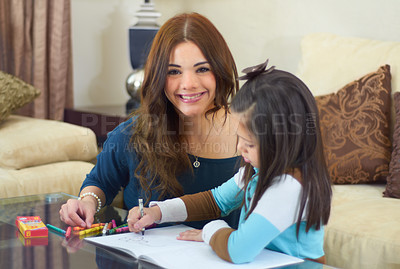 Buy stock photo Little girl getting help with her homework from her nanny