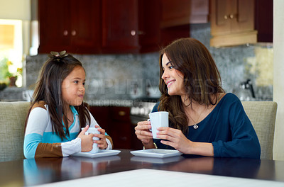 Buy stock photo Sweet little girl sharing a hot chocolate with her mother at home