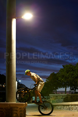 Buy stock photo Shot of a man doing tricks on his bike at night under a street light