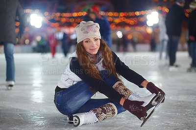 Buy stock photo Portrait of an attractive young woman sitting on an ice rink stretching her arms