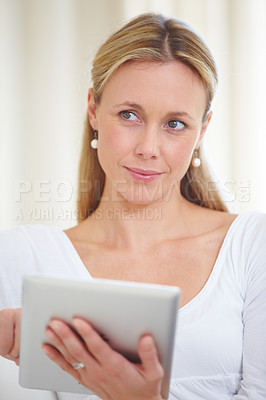Buy stock photo An beautiful young woman sitting at home with her digital tablet