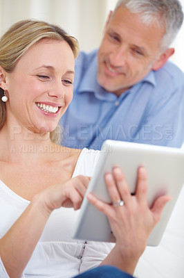 Buy stock photo An attractive young woman using her digital tablet with her husband standing behind her