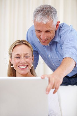 Buy stock photo A happy young woman using her laptop with her husband standing behind her