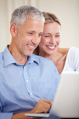 Buy stock photo A married couple smiling while sharing their laptop
