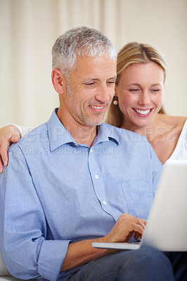 Buy stock photo A married couple sitting down together with their laptop
