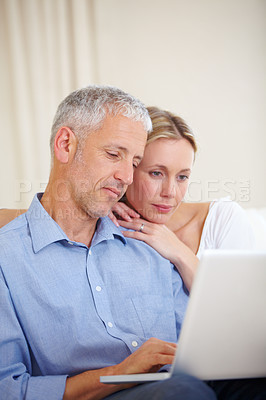 Buy stock photo A married couple sitting with their laptop at home