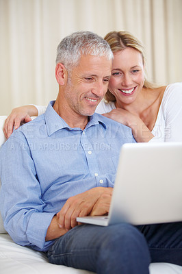 Buy stock photo A married couple looking happy as they work on their laptop