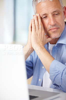 Buy stock photo A mature man looking somewhat disappointed while sitting at the laptop