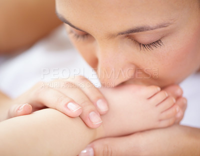 Buy stock photo A beautiful young mother kissing her baby's feet