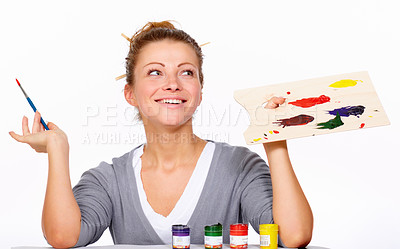 Buy stock photo Studio shot of an attractive young woman holding a paintbrush and palette isolated on white