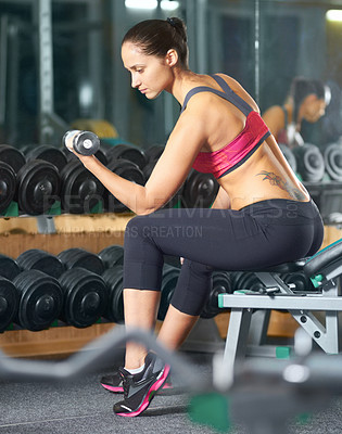 Buy stock photo Shot of an attractive young woman lifting weights in the gym