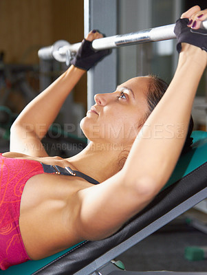 Buy stock photo Shot of an attractive young woman lifting a barbell in the gym