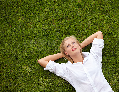 Buy stock photo High angle shot of an attractive young woman relaxing on a grassy field and looking up at the sky