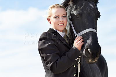 Buy stock photo Low angle portrait of a young female rider hugging her horse affectionately