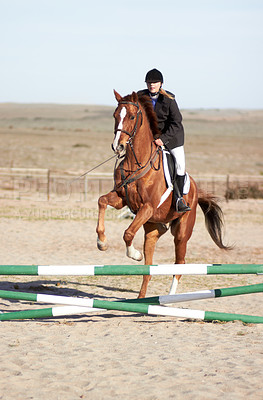 Buy stock photo Shot of a rider leading her horse over a jump