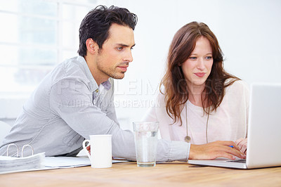 Buy stock photo Shot of a two young design professionals sitting together and working on a laptop