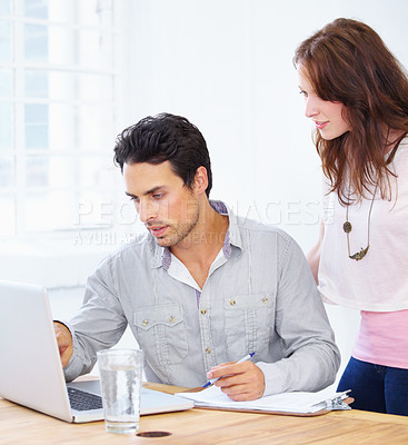 Buy stock photo Shot of a two young design professionals discussing something on a laptop