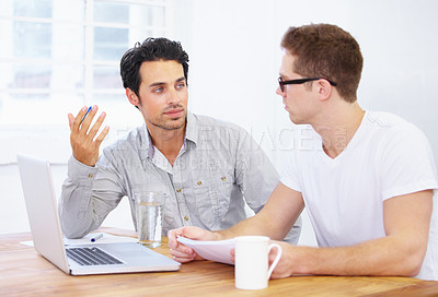 Buy stock photo Shot of two young professionals having a conversation over a laptop
