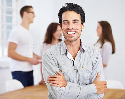 Buy stock photo Portrait of a happy-looking young business professional standing with his arms folded with coworkers talking in the background