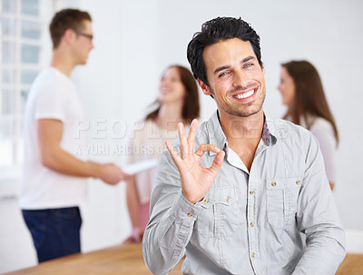 Buy stock photo Portrait of a young business professional giving the A-OK sign with coworkers talking in the background