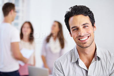 Buy stock photo Portrait of a young business professional standing with his arms folded with coworkers talking in the background