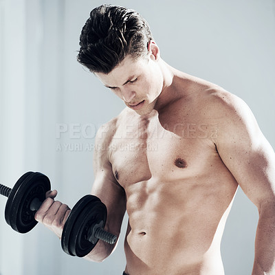 Buy stock photo A masculine male with no shirt on lifting weights and looking down