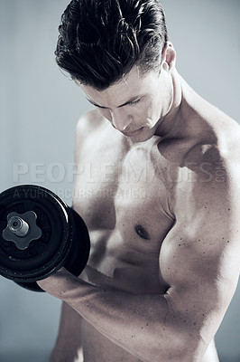 Buy stock photo A handsome man lifting a weight and looking at his biceps